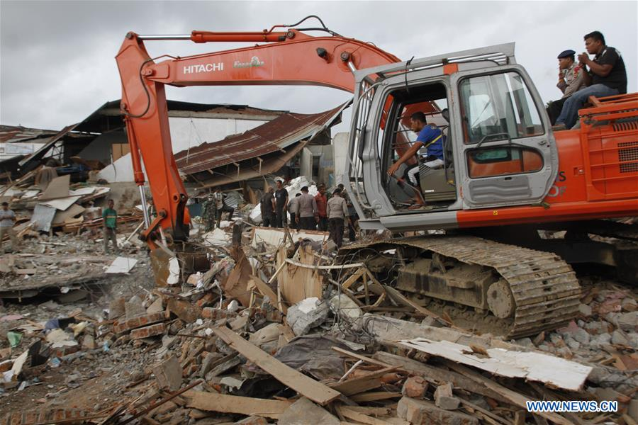 An excavator of Search and Rescue (SAR) team works on the debris in quake-hit Pidie Jaya district, Aceh, Indonesia, Dec. 7, 2016. At least 97 people have been killed and over 600 others suffered from wounds after a powerful and shallow underland quake hit western Indonesia