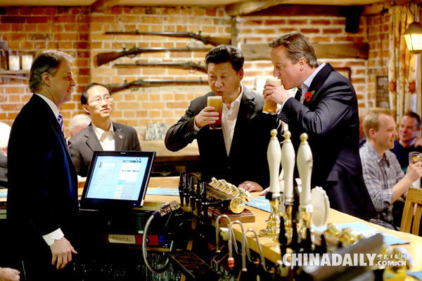 President Xi Jinping drinks a pint of beer with British Prime Minister David Cameron at The Plough at Cadsden pub in Princes Risborough, northwest of London, on Oct 22, 2015. The two leaders met for talks and dinner during a four-day state visit hailed as landmark by both China and Britain. [Photo/China Daily]