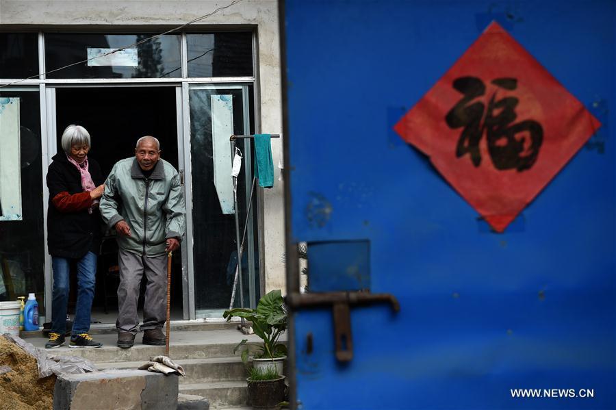 Zhang Fuzhi (à droite), aidé par sa fille Zhang Shouyun, descend les escaliers de sa maison, le 16 novembre 2016. Zhang Fuzhi, né en octobre 1927, a été battu par des soldats japonais en 1937. Il a perdu son œil droit. M. Zhang est décédé le 26 novembre 2016. Le 13 décembre 1937, les troupes japonaises occupèrent Nanjing, dans l