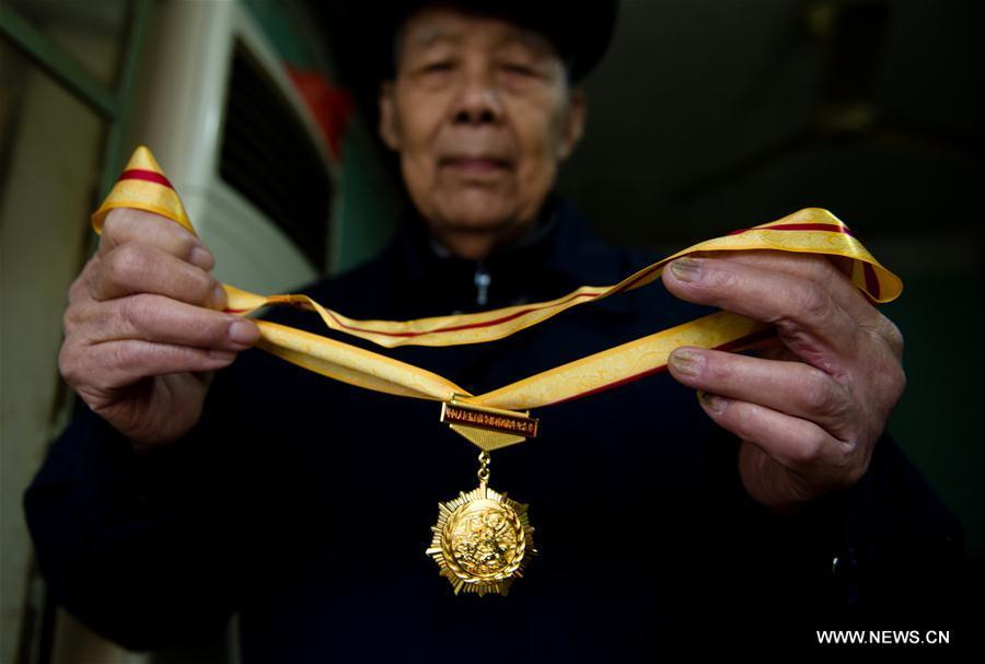 Li Gaoshan montre une médaille commémorant le 70e anniversaire de la victoire de la Guerre de Résistance du Peuple chinois contre l