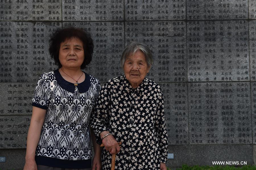 Ma Xiuying (à droite) et sa belle-fille posent pour la photo devant le mur des lamentations du Mémorial du Souvenir des victimes du Massacre de Nanjing par les envahisseurs japonais, à Nanjing, capitale de la province du Jiangsu (Est de la Chine), le 17 juin 2016.