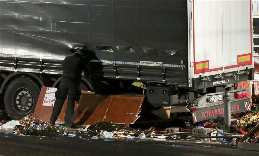 A German police officer looks into a truck at a Berlin Christmas market following an accident with the truck on Breitscheidplatz square near the fashionable Kurfuerstendamm avenue in the west of Berlin, Germany, Dec 19, 2016.