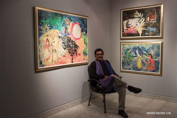 في الصورة الملتطقة يوم 20 ديسمبر، الفنان التشكيلي المصري محمد عبلة يجلس بجانب أعماله في المعرض
