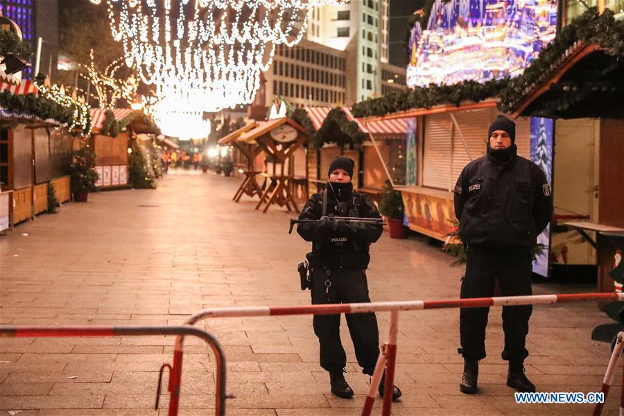 Police officers stand guard near the attacked Christmas market in Berlin, capital of Germany, on Dec. 21, 2016. German police is searching nationwide for a 23-year-old man under suspect after a lorry ploughed into a crowd at a Christmas market in Berlin on Monday night, killing 12 people and injuring many others. (Xinhua/Shan Yuqi)