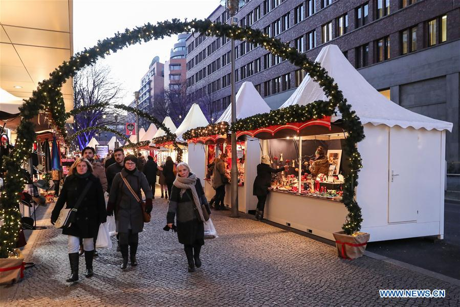 People wander through the reopened Christmas market at the Potsdamer Platz in Berlin, capital of Germany, on Dec. 21, 2016. Several Christmas markets in Berlin shut down due to safety concerns on Tuesday, were reopened on Wednesday. (Xinhua/Shan Yuqi)
