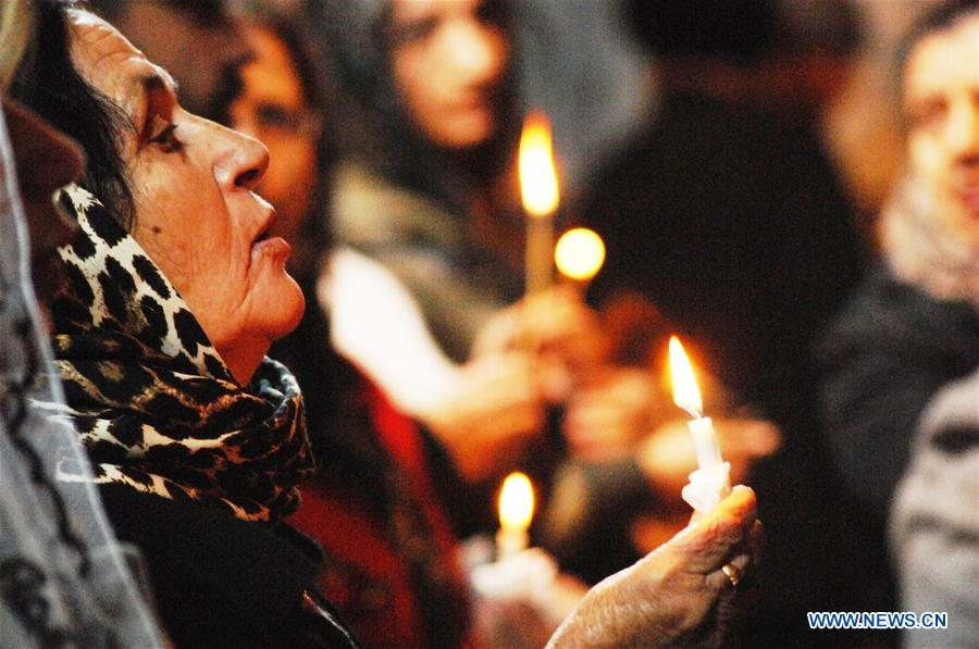 A woman holds a candle during the Christmas Mass in Bartella town, about 20 KM east of Mosul city in northern Iraq, on Dec. 24, 2016. About one hundred people gathered in Bartella town in northern Iraq on Saturday to attend the Christmas Mass. (Xinhua/Khalil Dawood)