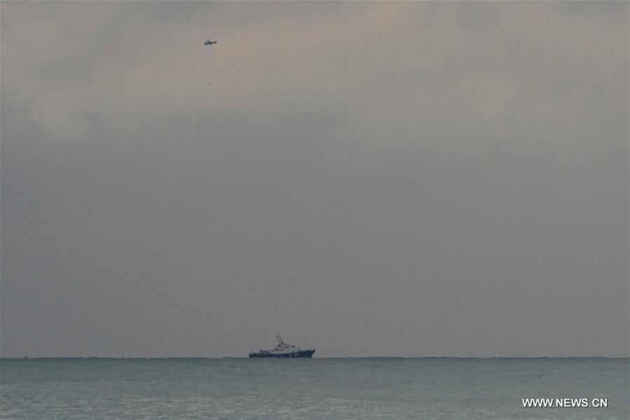 Photo taken on Dec. 25, 2016 shows a vessel and a helicopter taking part in a rescue operation on the Black Sea coast at the crash site of Russian Defense Ministry
