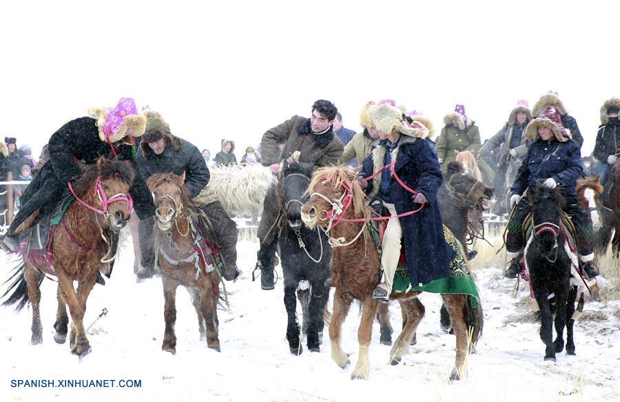 """XINJIANG, diciembre 25, 2016 (Xinhua) -- Imagen del 24 de diciembre de 2016, de miembros del grupo étnico Kazak participando en un partido de Buzkashi durante un festival local de hielo y nieve en la prefectura de Hami, en la Región Autónoma Uygur de Xinjiang, en el noroeste de China. Buzkashi, un evento deportivo tradicional que significa """"agarrar a la cabra"""", fue catalogado como patrimonio cultural intangible del estado en 2008. (Xinhua/Li Hanchi)"""