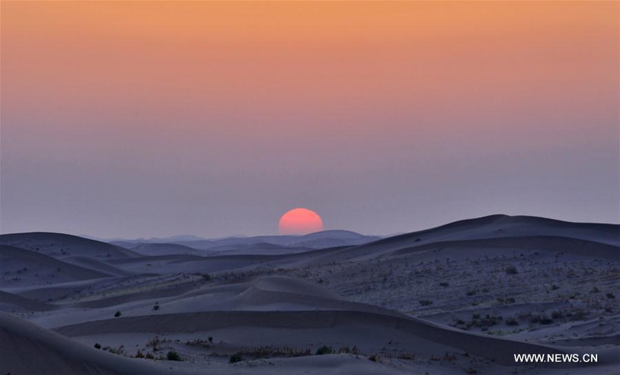 Photo prise le 5 août 2016 montrant le lever du soleil dans un désert à Wuwei, dans la province du Gansu (nord-ouest de la Chine). (Xinhua/Jiang Aiping)