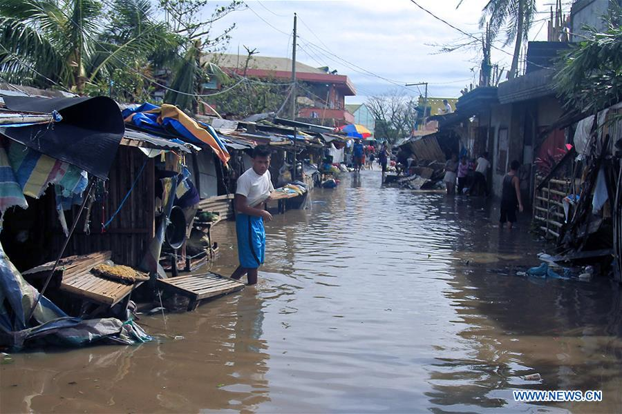 A resident wades through the flood brought by Typhoon Nock-Ten in Albay Province, the Philippines, Dec. 26, 2016. Typhoon Nock-Ten is battering provinces south of Manila, leaving at least three people dead, police and local officials said on Monday. (Xinhua/Stringer)