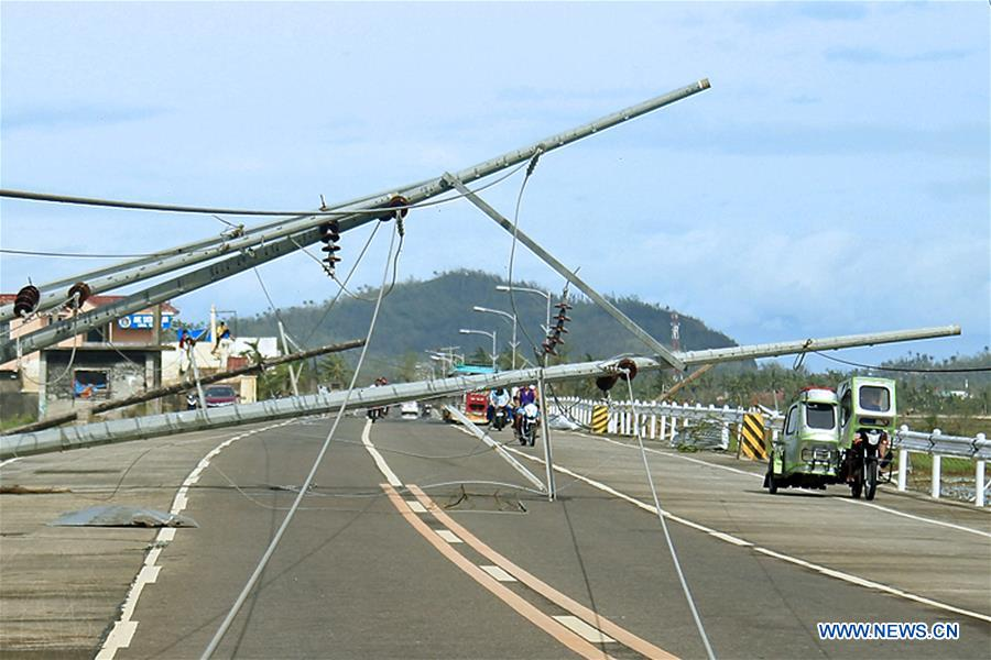 Residents pass by electric poles toppled by strong winds from Typhoon Nock-Ten in Albay Province, the Philippines, Dec. 26, 2016. Typhoon Nock-Ten is battering provinces south of Manila, leaving at least three people dead, police and local officials said on Monday. (Xinhua/Stringer)
