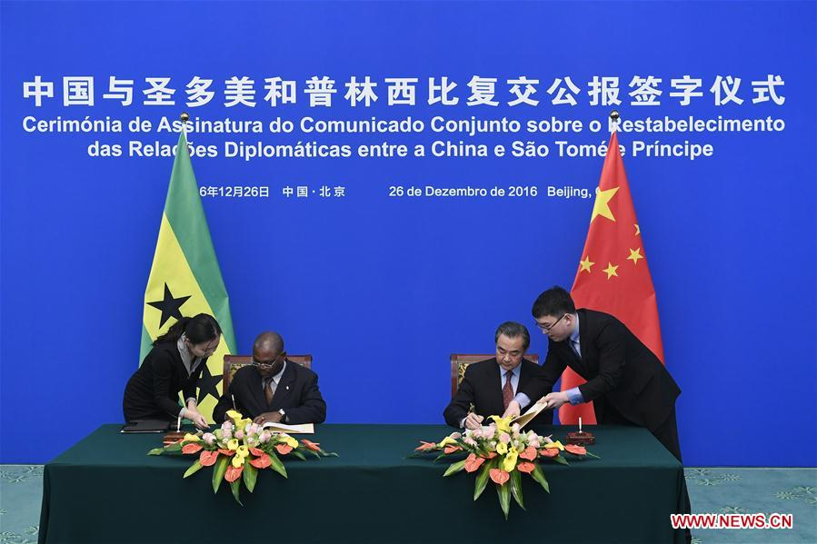 Chinese Foreign Minister Wang Yi (R) and his counterpart of Sao Tome and Principe Urbino Botelho sign a joint communique after their talks to resume the diplomatic relations between China and Sao Tome and Principe, in Beijing, capital of China, Dec. 26, 2016. (Xinhua/Yan Yan)