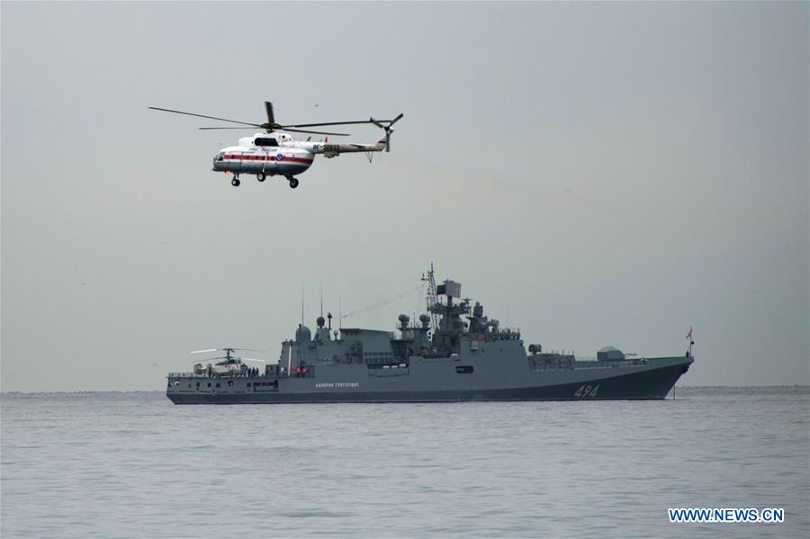 Photo taken on Dec. 27, 2016 shows a navy ship and a helicopter taking part in a rescue operation on the Black Sea coast at the crash site of Russian Defense Ministry