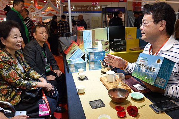 A tea merchant from Taiwan (right) showcases his tea sets at a tea expo held in Fujian province that attracted businessmen and tea lovers from across the Taiwan Straits. [Photo/Xinhua]