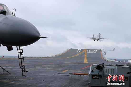 """The """"Flying Shark"""" jet fighter takes off from the deck on a signal given by a crew member. Refueling in the sky and air-defense confrontation were also part of the training exercise. [Photo: chinanews.com]"""
