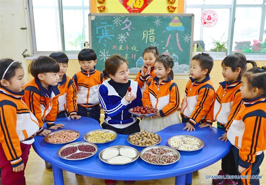 HEBEI, enero 4, 2017 (Xinhua) -- Una maestra muestra los ingredientes de la sopa de arroz Laba a los niños en un jardín de niños en Xingtai, provincia de Hebei, en el norte de China, el 4 de enero de 2017. El Festival Laba, una celebración tradicional china llevada a cabo en el día diez del duodésimo mes del calendario lunar, caerá el 5 de enero este año. Es costumbre en este día comer una especial sopa de arroz Laba, o gachas de ocho tesoros, usualmente elaborada con al menos ocho ingredientes, que representan las oraciones del pueblo para la cosecha, la felicidad y la paz. (Xinhua/Zhu Xudong)