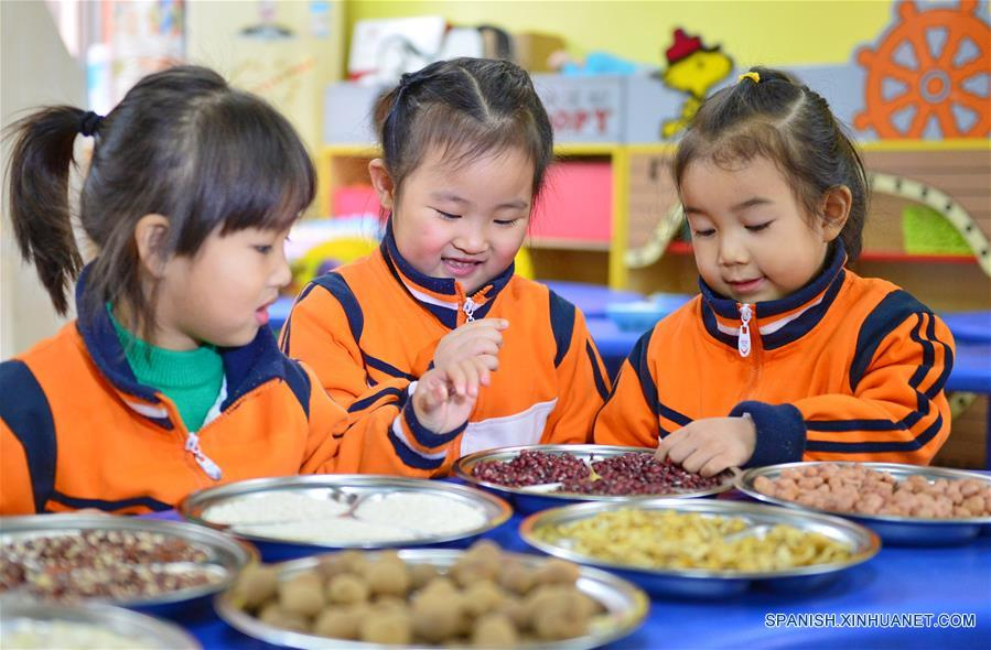 Niñas observan los ingredientes de la sopa de arroz Laba en un jardín de niños en Xingtai, provincia de Hebei, en el norte de China, el 4 de enero de 2017. El Festival Laba, una celebración tradicional china llevada a cabo en el día diez del duodésimo mes del calendario lunar, caerá el 5 de enero este año. Es costumbre en este día comer una especial sopa de arroz Laba, o gachas de ocho tesoros, usualmente elaborada con al menos ocho ingredientes, que representan las oraciones del pueblo para la cosecha, la felicidad y la paz. (Xinhua/Zhu Xudong)