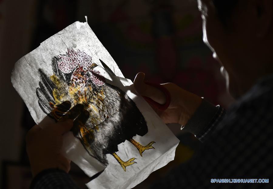 Wei Guoqiu, perteneciente a la cuarta generación de artesanos del Cometa Wei, muestra cometas con forma de gallo para celebrar el próximo Año Nuevo lunar chino, en su estudio en Tianjin, en el norte de China, el 4 de enero de 2017. La elaboración de cometas es una artesanía popular tradicional china, y el Cometa Wei de Tianjin es famoso por su desarrollo de unos 200 cometas con muchos nuevos diseños. (Xinhua/Lian Yi)