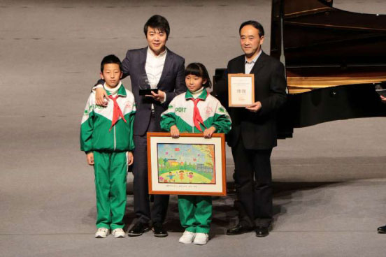 Lang Lang poses for photos with two representatives of left-behind children in Linxia, Gansu province. [Photo: china.org.cn]