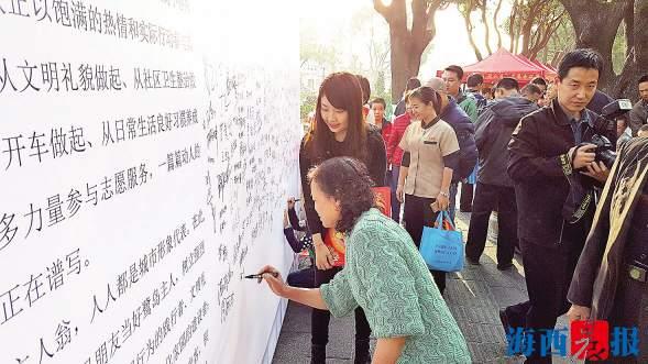 签名墙吸引了众多民众驻足、签名。