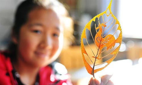 "A student shows the leaf carving work ""Rooster"" of Liu Ping, an art teacher of Qingdao Experimental Primary School, east China"
