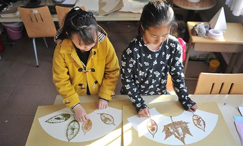 "Students show the leaf carving works ""Rooster"" of Liu Ping, an art teacher of Qingdao Experimental Primary School, east China"