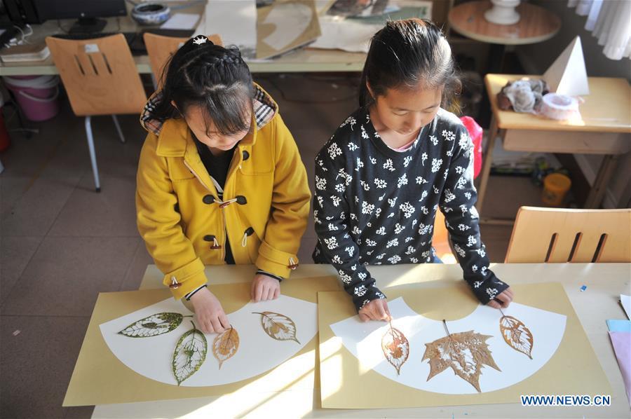 Deux élèves présentent les feuilles découpées