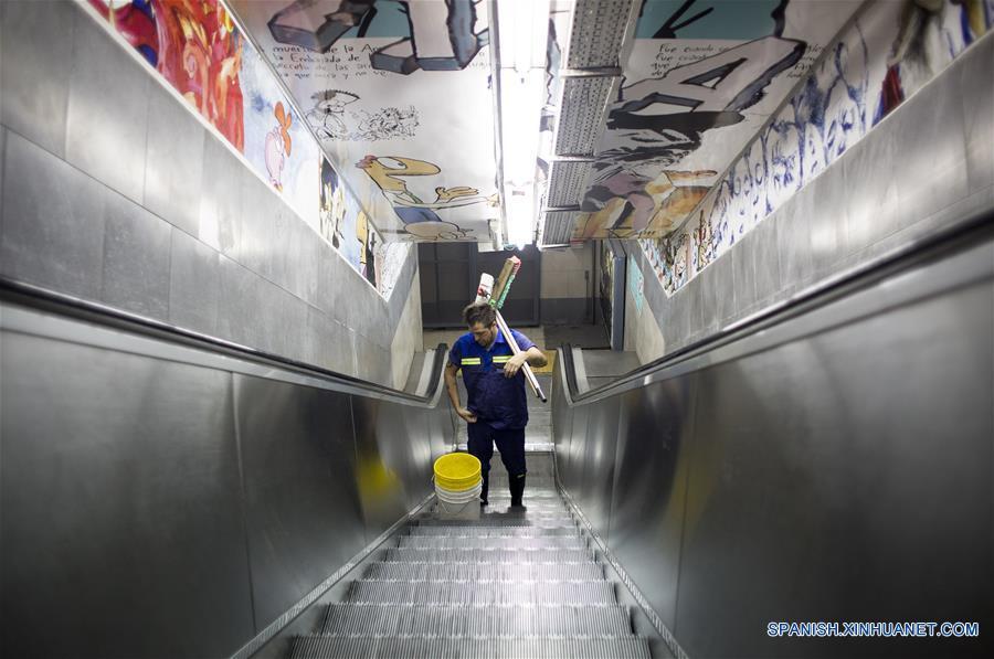 """Imagen del 10 de diciembre de 2016 del escritor argentino, Enrique """"Kike"""" Ferrari, trasladándose por medio de una escalera eléctrica con sus elementos de trabajo en la estación Pasteur-AMIA de la línea B del Metro donde trabaja en el turno nocturno de limpieza, en Buenos Aires, Argentina. Ferrari, quien trabaja de 11 de la noche a cinco de la mañana en la estación, transmite su pasión por la escritura, por la que ha sido premiado y traducido al francés y el italiano, y la forma en que conjuga esa actividad con la limpieza. Escritor de novelas y cuentos del género negro premiado en Argentina, España, Francia y Cuba, admite que trabajar de noche le """"dificultó la estructura"""". Me gusta escribir de mañana. Me despertaba temprano los sábados y domingos para escribir hasta el mediodía. Pero con la rutina de trabajar en la madrugada, el formato de escritura debió cambiar. Ferrari rescató las posibilidades que abre el hecho de estar despierto cuando la mayoría de los """"porteños"""" duerme. """"Así como molesta el horario, acompaña un poco la soledad, el silencio. Estar en un lugar en el que no hay nadie más que nosotros, haciendo un trabajo que requiere esfuerzo físico, me sirve"""", puntualizó. (Xinhua/Martín Zabala)"""