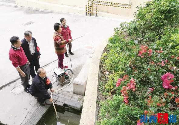 老人督导队在为小区绿化浇水。