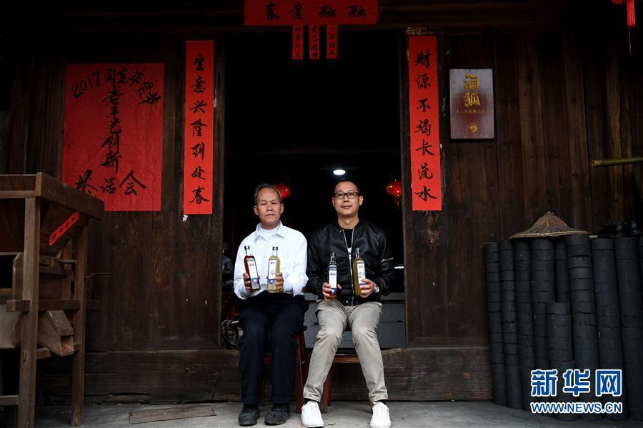 Huang Baofeng(izquierdo) y Yang Tianji mostran los productos del vino de arroz, el 11 de enero de 2017.