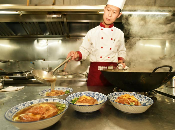 Sun Jinyong, chief cook from a hotel in Fengyang in Shanxi province, cooks Ba Da Wan, Jan 11, 2017. [Photo/Xinhua]