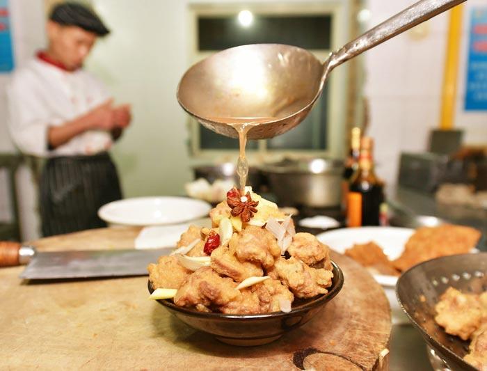 Sun cooks braised pork ribs, one dish of Fengyang Ba Da Wan, Jan 11, 2017. [Photo/Xinhua]