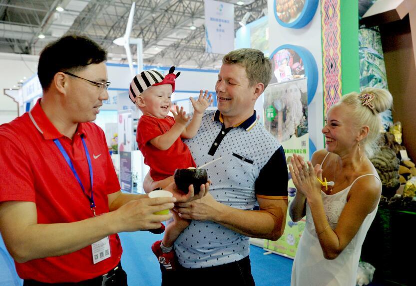 来自俄罗斯的一件人在国际旅游岛展区品尝海南椰子食品
