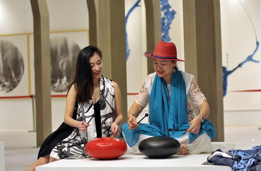 """两位女性艺术工作者在交流""""钢舌鼓""""的演奏"""