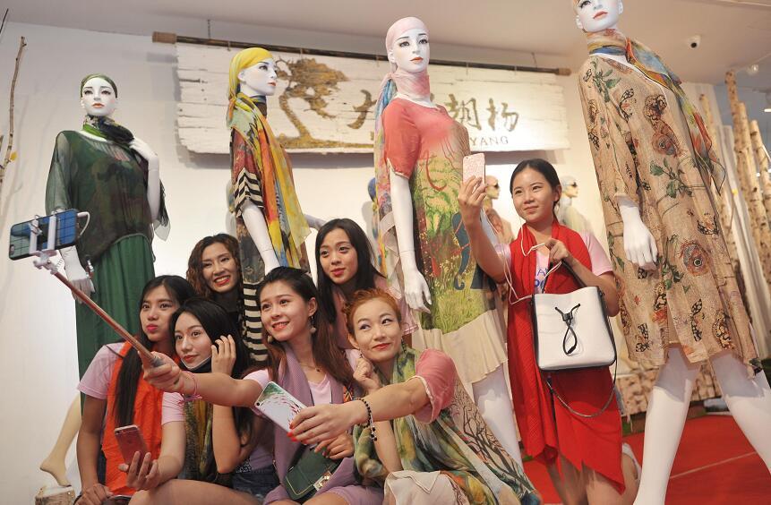 美女主播们在旅游文化商品展区现场促销丝绸时装