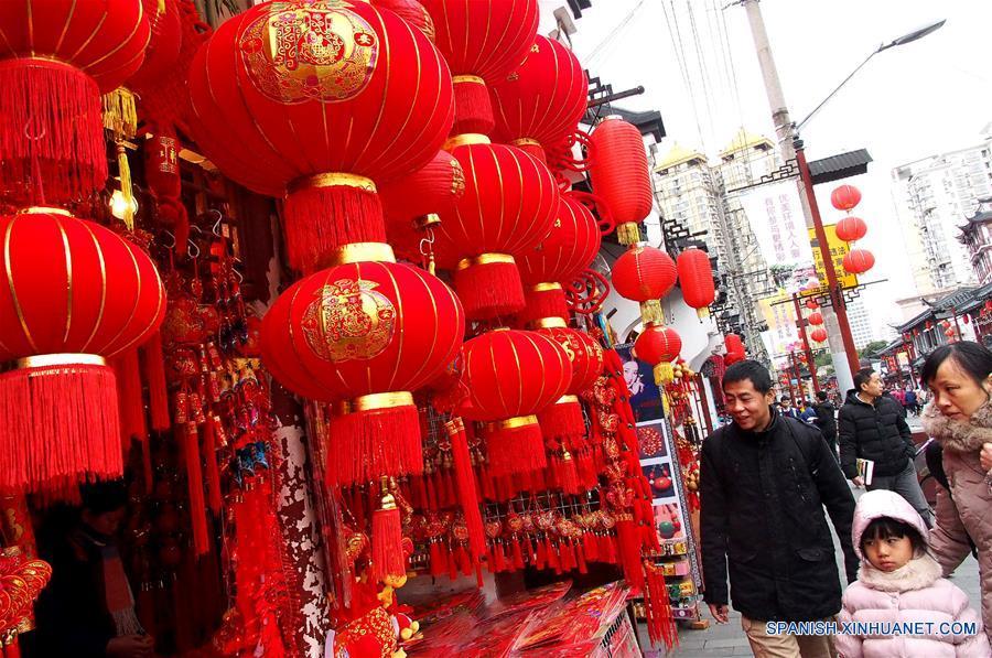 SHANGHAI, enero 15, 2017 (Xinhua) -- Personas caminan frente a decoraciones de Año Nuevo en el mercado Chenghuangmiao en Shanghai, en el este de China, el 15 de enero de 2017. Elementos tradicionales chinos son exhibidos en las calles de Shanghai para recibir el próximo Festival de Primavera o Año Nuevo Lunar del Gallo que se festeja este año el 28 de enero. (Xinhua/Chen Fei)