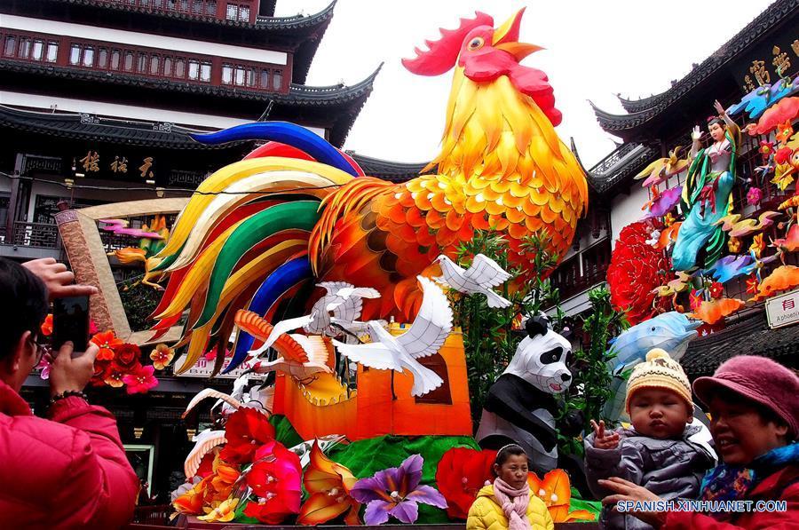 SHANGHAI, enero 15, 2017 (Xinhua) -- Personas posan frente a una linterna en forma de gallo en el mercado Chenghuangmiao en Shanghai, en el este de China, el 15 de enero de 2017. Elementos tradicionales chinos son exhibidos en las calles de Shanghai para recibir el próximo Festival de Primavera o Año Nuevo Lunar del Gallo que se festeja este año el 28 de enero. (Xinhua/Chen Fei)