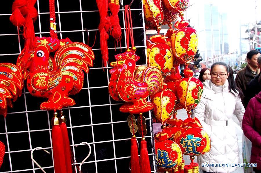 SHANGHAI, enero 15, 2017 (Xinhua) -- Personas caminan cerca de decoraciones de Año Nuevo en el mercado Chenghuangmiao en Shanghai, en el este de China, el 15 de enero de 2017. Elementos tradicionales chinos son exhibidos en las calles de Shanghai para recibir el próximo Festival de Primavera o Año Nuevo Lunar del Gallo que se festeja este año el 28 de enero. (Xinhua/Chen Fei)