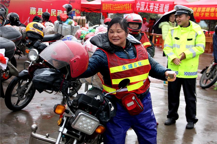 Sacudiendo la lluvia del casco, la abuela Zhang entró en  la estación para descansar