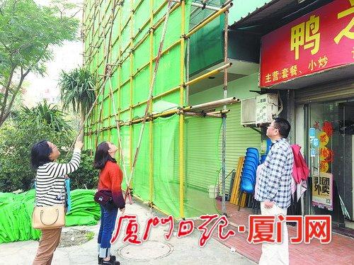 社区工作人员在查看脚手架是否影响商家的店招。