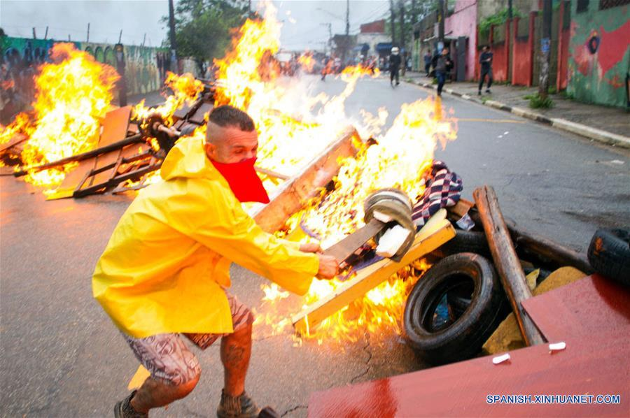 Un hombre prende fuego a un barricada durante un enfrentamiento entre policías y residentes por el desalojo de un predio particular, en el barrio São Mateus, en el este de Sao Paulo, Brasil, el 17 de enero de 2017. El líder del Movimiento de los Trabajadores Sin Techo (MTST) de Brasil, Guilherme Boulos, fue detenido el martes en Sao Paulo por desacato a la autoridad cuando apoyaba a unas 6,000 personas desalojadas por la policía de un terreno particular en el oriente de Sao Paulo, informaron sus abogados. Los desalojados montaron barricadas para impedir el acceso de la policía, que respondió con el uso de gases lacrimógenos para dispersar a los manifestantes. (Xinhua/Paulo Ermantino/RAW IMAGE/ESTADÃO CONTEÚDO/AGENCIA ESTADO)