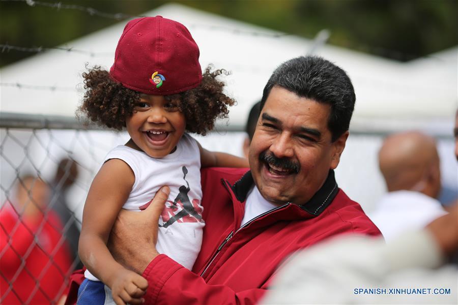 """CARACAS, enero 22, 2017 (Xinhua) -- Imagen cedida por la Presidencia de Venezuela, del presidente venezolano, Nicolás Maduro (d), cargando a un niño durante el programa Los Domingos con Maduro, en la parroquia San José en Caracas, Venezuela, el 22 de enero de 2017. De acuerdo con información de la prensa local, Maduro destacó durante su programa los beneficios de obtener el nuevo """"Carnet de la Patria"""", instrumento impulsado el gobierno venezolano para fortalecer y expandir el sistema de protección social. (Xinhua/Presidencia de Venezuela)"""