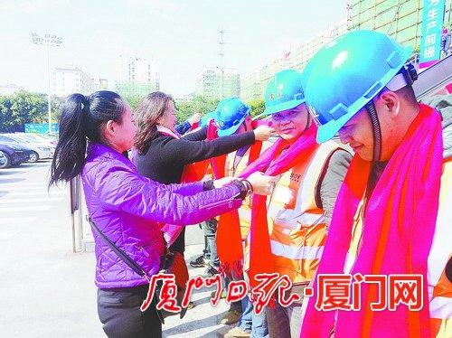禾山社区巾帼志愿者为建设者送上红围巾。( 本报记者 郭筱淳 摄)