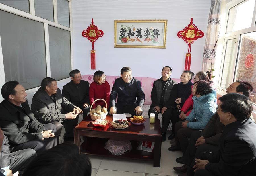 Chinese President Xi Jinping talks with villagers and local cadre at the home of villager Xu Haicheng in Desheng Village, Xiaoertai Township of Zhangbei County in north China