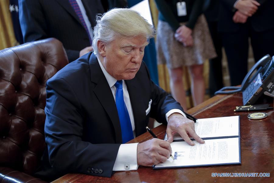 """El presidente estadounidense, Donald Trump, firma una de las cinco ordenes ejecutivas relacionadas con la industria de oleoductos, en la Oficina Oval de la Casa Blanca en Washington D.C., Estados Unidos de América, el 24 de enero de 2017. El presidente de Estados Unidos de América, Donald Trump, firmó el martes una orden ejecutiva para reactivar los controvertidos oleoductos Keystone XL y Dakota Access. Trump dijo a los reporteros que Estados Unidos de América """"va a renegociar algunos de los términos"""" del proyecto Keystone XL. El oleoducto Dakota estará """"sujeto a los términos y condiciones negociados por nosotros"""", afirmó. (Xinhua/Shawn Thew/CNP/ZUMAPRESS)"""