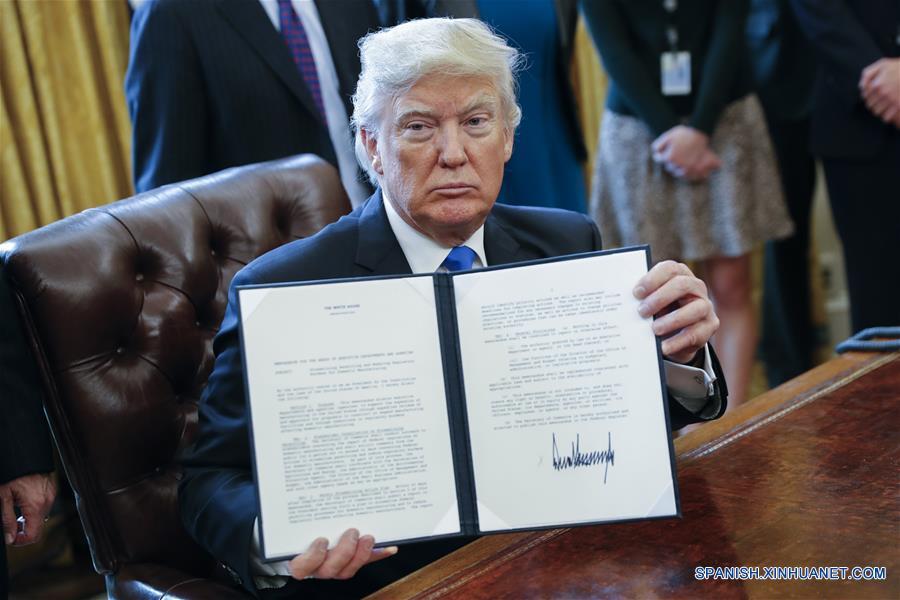"""WASHINGTON D.C., enero 24, 2017 (Xinhua) -- El presidente estadounidense, Donald Trump, muestra una de las cinco ordenes ejecutivas firmadas relacionadas con la industria de oleoductos, en la Oficina Oval de la Casa Blanca en Washington D.C., Estados Unidos de América, el 24 de enero de 2017. El presidente de Estados Unidos de América, Donald Trump, firmó el martes una orden ejecutiva para reactivar los controvertidos oleoductos Keystone XL y Dakota Access. Trump dijo a los reporteros que Estados Unidos de América """"va a renegociar algunos de los términos"""" del proyecto Keystone XL. El oleoducto Dakota estará """"sujeto a los términos y condiciones negociados por nosotros"""", afirmó. (Xinhua/Shawn Thew/CNP/ZUMAPRESS)"""