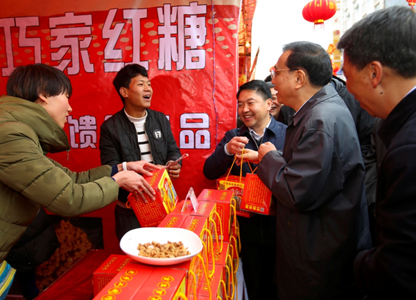 Premier Li bought several boxes of cane sugar after a short walk around the more than 20 stalls in an unexpected visit to the street on the morning of Jan 23.