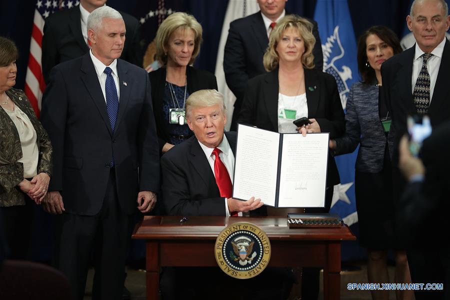 El presidente de Estados Unidos de América, Donald Trump (frente), muestra el documento luego de la firma de una orden ejecutiva para reforzar la seguridad fronteriza, en el Departamento de Seguridad Nacional, en Washington, D.C., capital de Estados Unidos de América, el 25 de enero de 2017. El presidente de Estados Unidos de América, Donald Trump, firmó el miércoles una orden ejecutiva para reforzar la seguridad fronteriza, antes de un discurso ya programado que pronunció en el Departamento de Seguridad Nacional. (Xinhua/Chip Somodevilla/CNP/ZUMAPRESS)