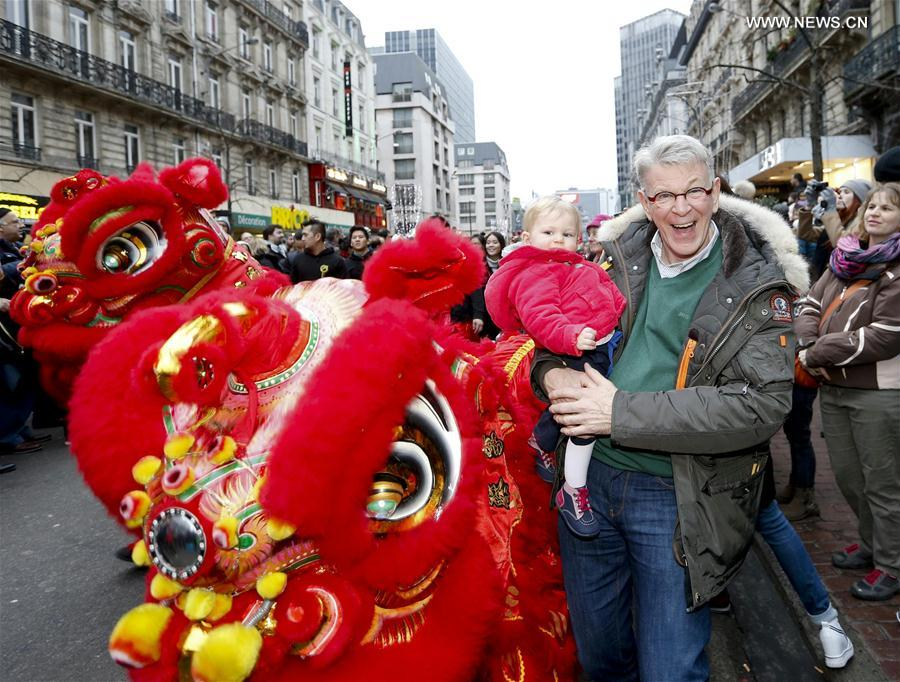 People interact with lion dance performers during the Chinese Lunar New Year Parade in downtown Brussels, Belgium, on Jan. 28, 2017. (Xinhua/Ye Pingfan)