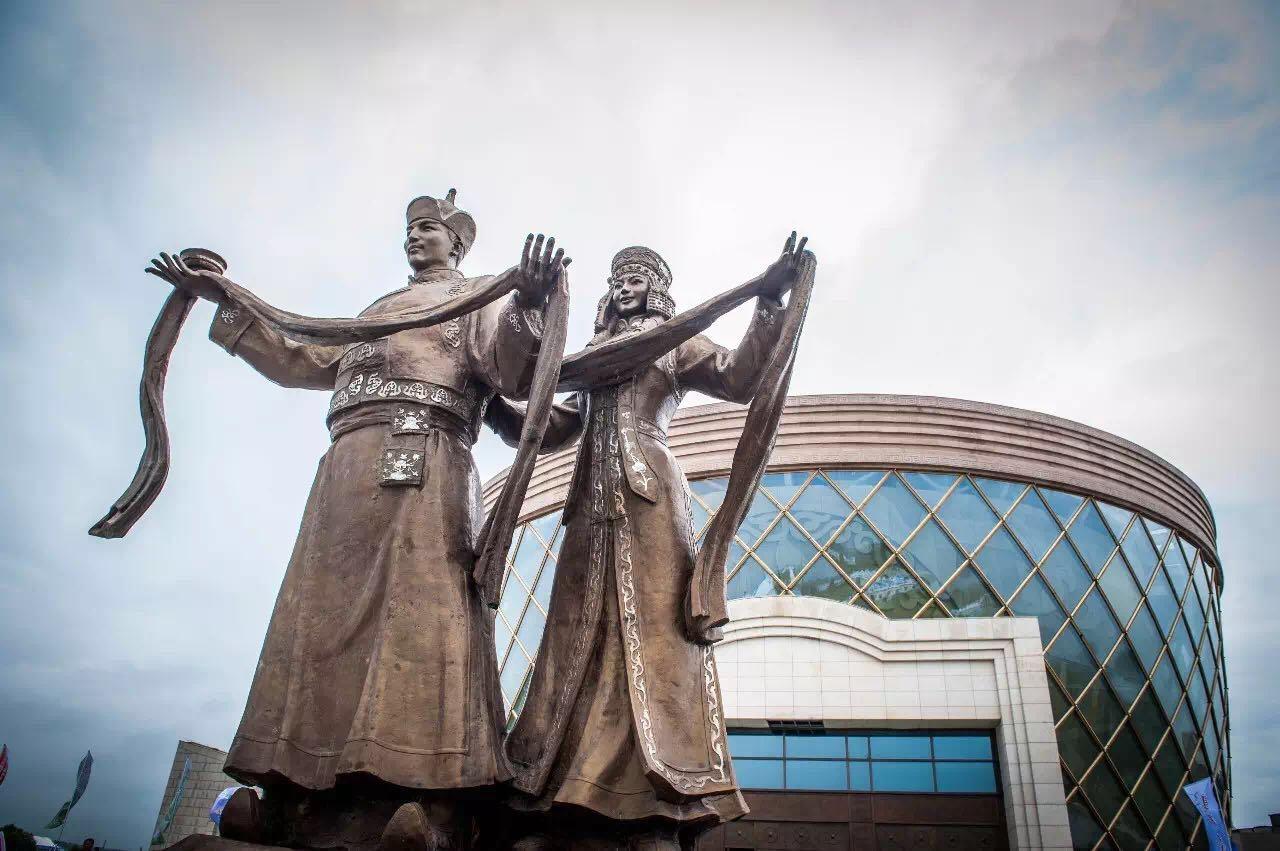"""那达慕大会是蒙古族传承至今的传统娱乐项目,包括博克(蒙古式摔跤)、射箭、赛马、马术表演等竞技运动,都已成为蒙古文化的一部分。大会在距离康巴什只有30多公里的成吉思汗陵举行。对于大多数游客来说,""""成吉思汗陵""""或许只是一座民族风貌多过古迹展品的博物馆。而对于世代忠诚的达尔扈特人来说却不一样,如今他们依然作为成吉思汗的守陵人,生活在从景区即可遥望的""""老陵""""中,日月祭祀,虔诚恭敬,守护着800年不灭的族之圣火。"""